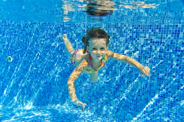 Happy smiling underwater child in swimming pool, beautiful girl swims and having fun. kids sport on family summer vacation. active holiday Premium Photo