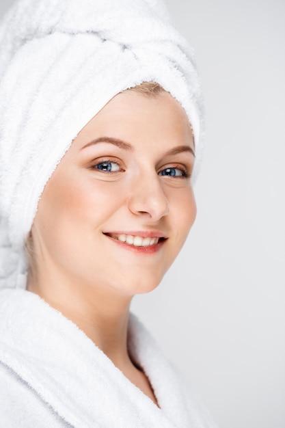 幸せな笑顔の女性は、フェイシャルクリーム、スキンケアコンセプトを適用します 無料写真