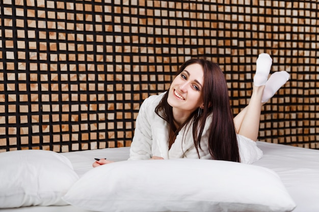 Happy smiling woman lying on the bed, caucasian brunette girl. Premium Photo