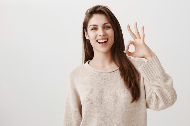 Donna sorridente felice che mostra il gesto giusto soddisfatto, approvare o raccomandare il prodotto Foto Gratuite