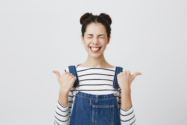 左と右の指を指している目を閉じて幸せな笑顔の女性 無料写真