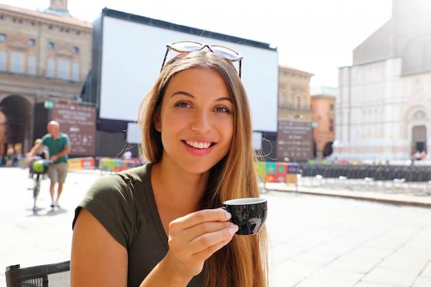 日当たりの良いイタリアの風景にコーヒーのカップと幸せな笑顔の女性 Premium写真