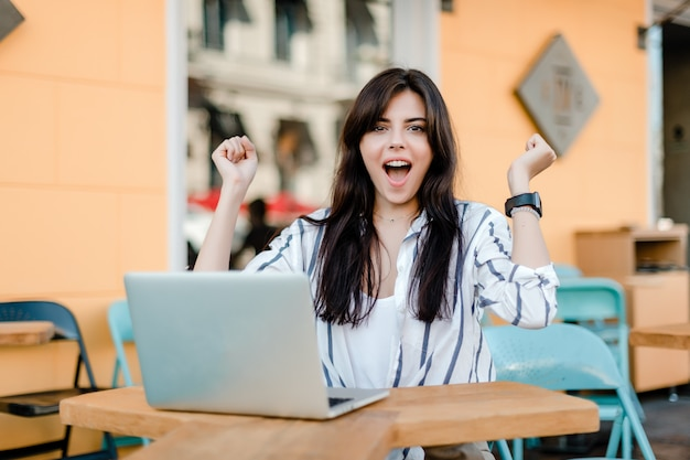 Happy smiling woman with laptop sitting outdoors in cafe Premium Photo