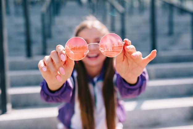長い髪の幸せな笑顔の女性はピンクのメガネを保持している明るいジャケットを着て、外で楽しんでいます 無料写真