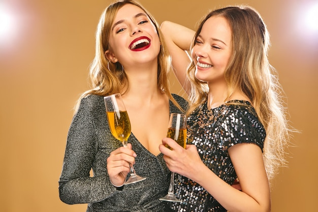 Happy smiling women in stylish glamorous dresses with champagne glasses on golden wall Free Photo