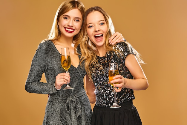 Happy smiling women in stylish glamorous dresses with champagne glasses Free Photo