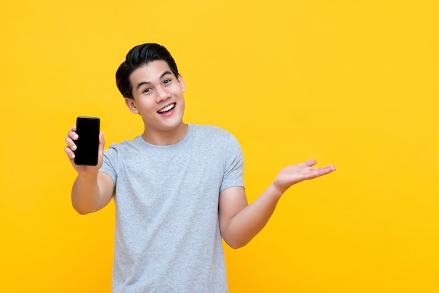 Happy smiling young asian man showing mobile phone with another hand open Premium Photo