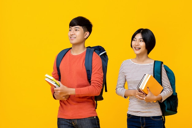 Happy smiling young asian students carrying books to school Premium Photo