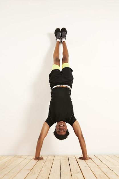 木の床の白い壁に逆立ちをしている黒と黄色のトレーニング服で幸せな笑顔の若い黒人モデル。 無料写真