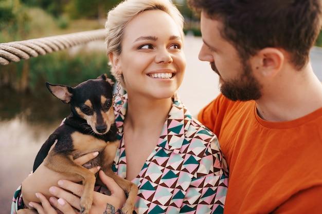 橋の上に犬を抱いて幸せな笑顔若いカップル 無料写真