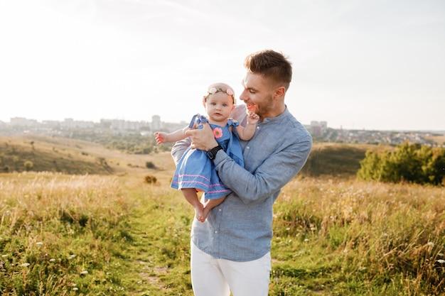 Счастливый улыбающийся молодой отец и маленькая дочь в его руках весело на открытом воздухе в летний день. концепция семьи отцы и детский день Premium Фотографии