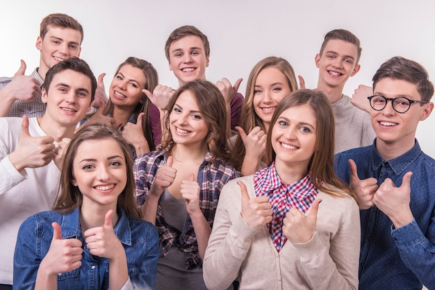 Happy smiling young group of friends with thumbs up. Premium Photo
