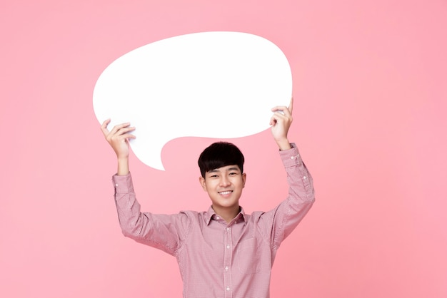 Happy smiling young handsome asian man holding speech bubble Premium Photo
