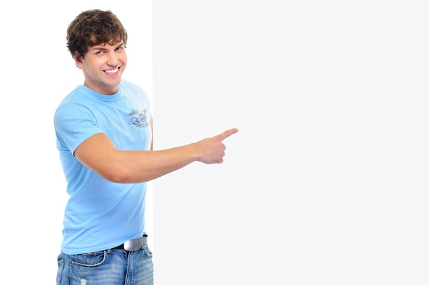 Giovane sorridente felice che mostra dal dito sulla bandiera vuota bianca Foto Gratuite