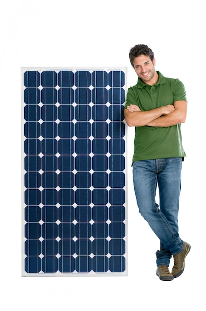 Happy smiling young man standing with a solar panel for renewable energy, isolated on white background Premium Photo