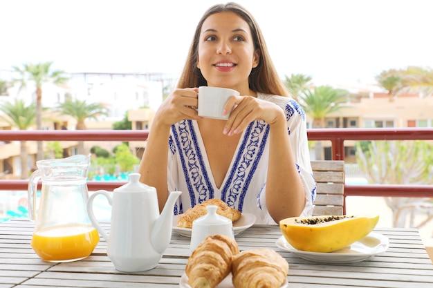 彼女の休暇のリゾートホテルで朝食を食べて幸せな笑顔若い女 Premium写真