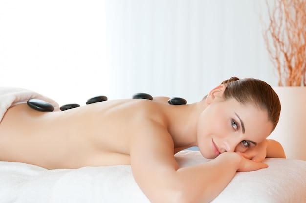 Счастливая улыбающаяся молодая женщина, лежащая с камнями на спине в спа-центре красоты Premium Фотографии