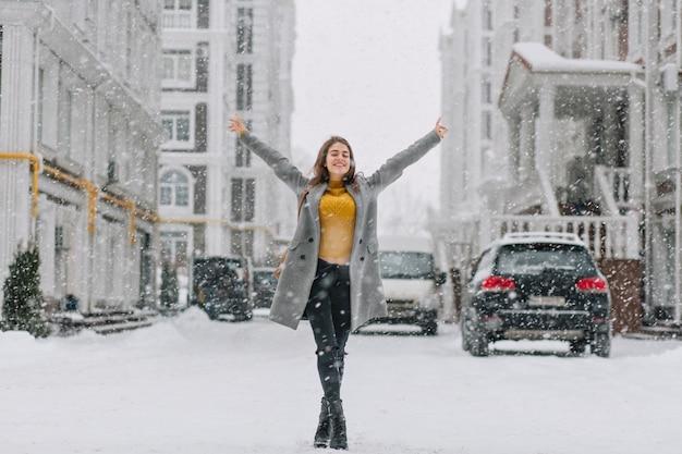 Счастливое снежное зимнее время в большом городе красивая девушка, наслаждающаяся снегопадом на улице. настоящие положительные эмоции, держась за руки вверху, Бесплатные Фотографии