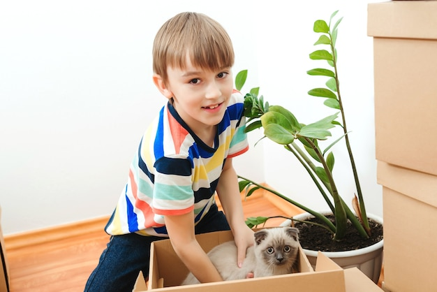 Happy son and a cat having fun together at moving day in new home. Premium Photo