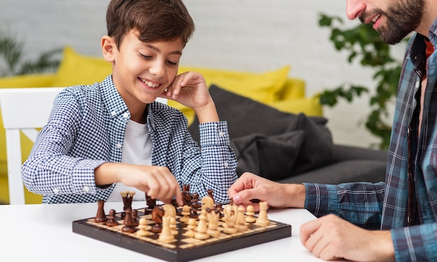 Happy son playing chess with his father Free Photo
