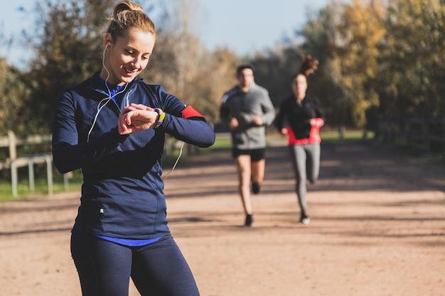 Happy sportswoman controlling her beats Premium Photo