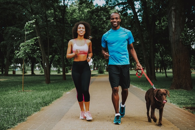 Happy sporty couple and brown cute dog. Premium Photo