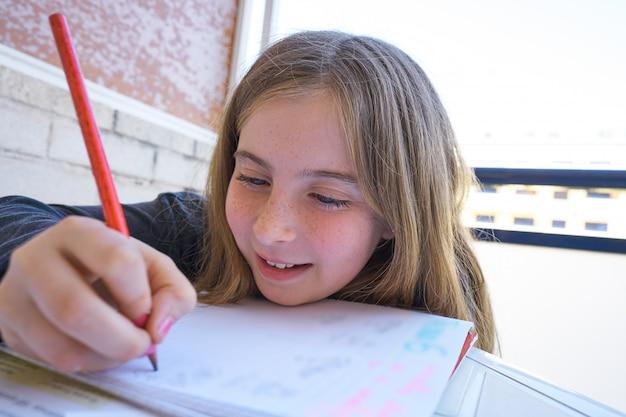 Happy student girl doing her homework Premium Photo