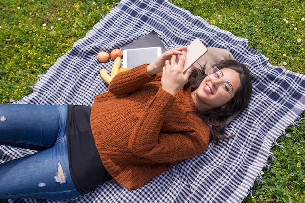 Happy student girl lying on grass Free Photo
