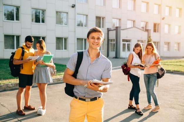 Studente felice con i taccuini e lo zaino che sorride mentre stando Foto Gratuite