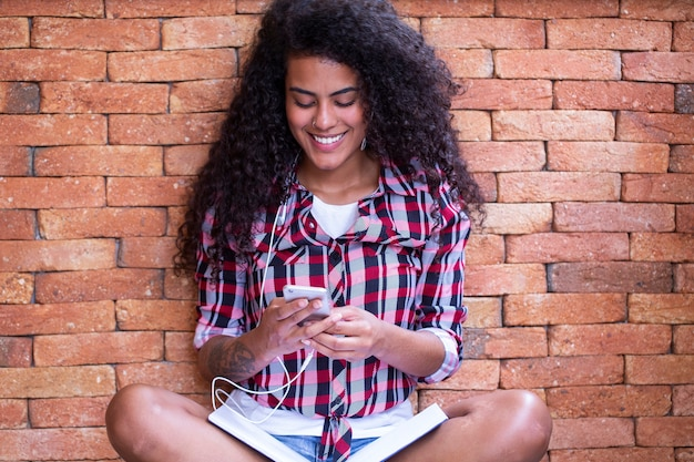 휴대 전화를 사용 하 고 웃 고 벽돌 벽 배경으로 앉아 아프로 헤어 스타일으로 행복 한 학생 여자. 프리미엄 사진