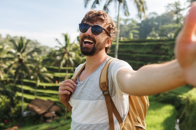 米のプランテーションでバックパック旅行と幸せなスタイリッシュな白人男性は、思い出のための自己肖像画を作ります。 無料写真