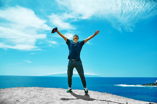 Happy stylish man in casual clothes standing on the cliff of mountain Free Photo