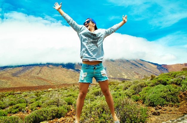 Happy stylish man in casual hipster clothes jumping in front of mountain with raised hands to the sun and celebrating success Free Photo