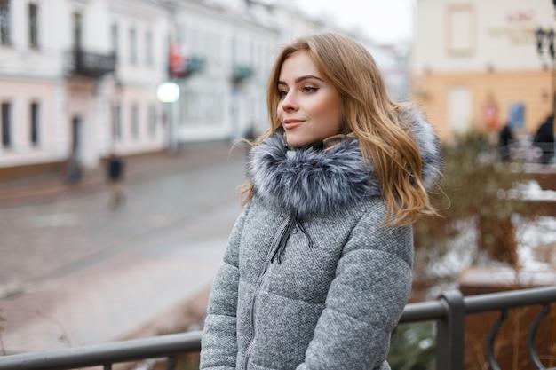 ファッショナブルな冬のコートを着た灰色のニットの帽子をかぶった幸せでスタイリッシュな若い女性は、冬の日に街を散歩します。かわいい女の子 Premium写真