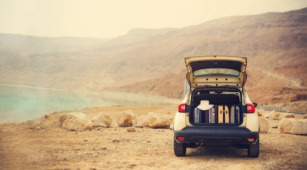 Happy stylish young woman traveler on beach road sitting on white crossover car Premium Photo