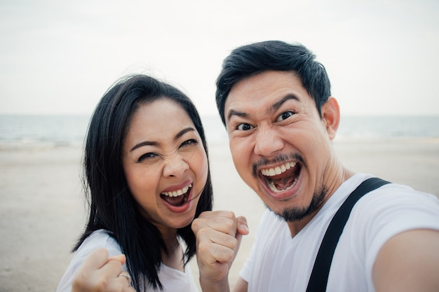 Happy and success yeah face of couple tourist on romantic beach vacation trip. Premium Photo