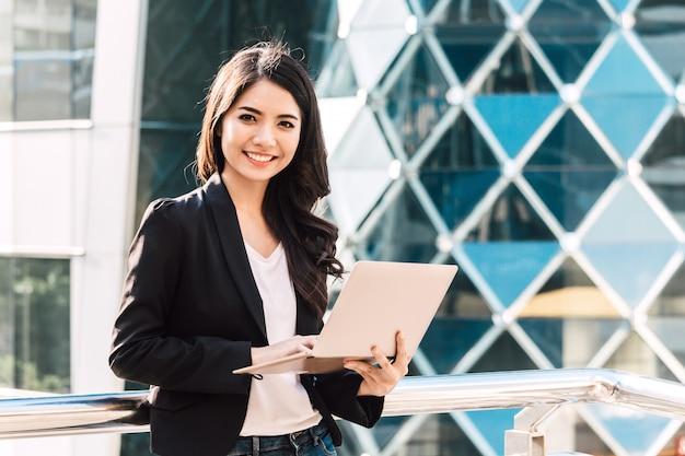 Happy successful businesswoman using a laptop computer Premium Photo