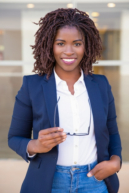 Happy successful sales agent posing near office Free Photo