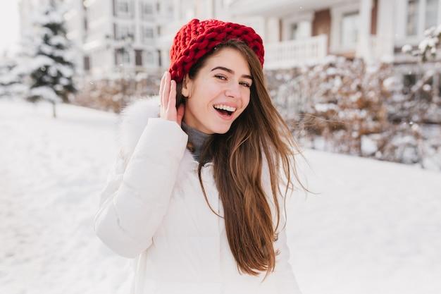 長いブルネットの髪が雪でいっぱいの通りで楽しんで、赤い帽子でうれしそうな若い女性の冬時間の幸せな日当たりの良い冷凍の朝。 無料写真