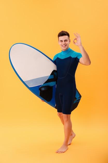 サーフボードを歩いて、okの標識を示す幸せなサーファー 無料写真