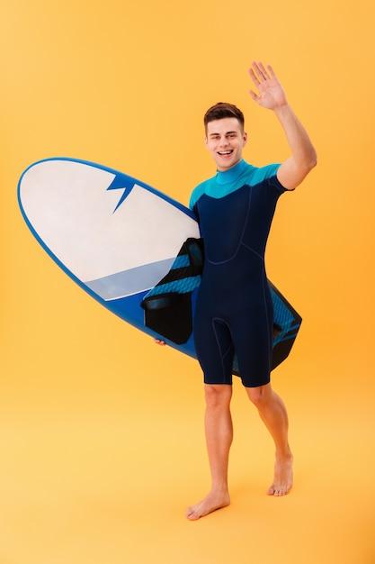 サーフボードと歩いて幸せなサーファー 無料写真