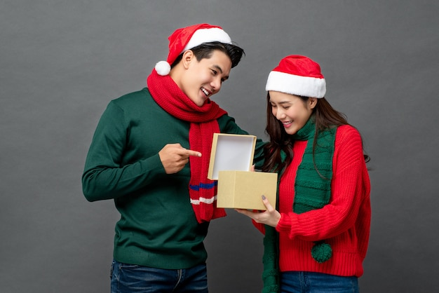 Happy surprised asian woman opening christmas gift box given by her boyfriend Premium Photo