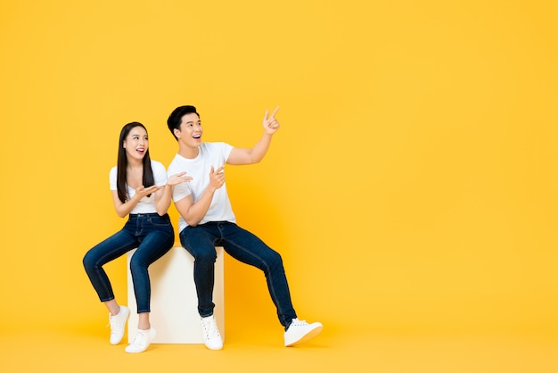 Happy surprised attractive young asian couple pointing and looking at blank space beside in yellow i