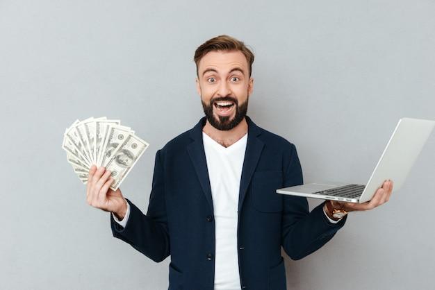 Счастливый удивленный бородатый человек в деловой одежде, держа деньги и портативный компьютер, глядя на камеру над серым Бесплатные Фотографии
