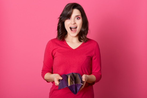 Happy surprised woman holding wallet full of money, win big sum of money, standing with widely opened mouth and excited facial expression, lady wearing red shirt. Free Photo