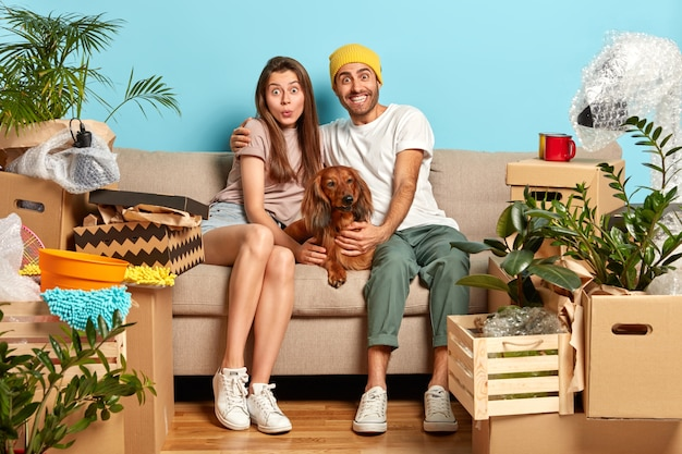 Happy surprised young woman and man embrace while sit on sofa Free Photo