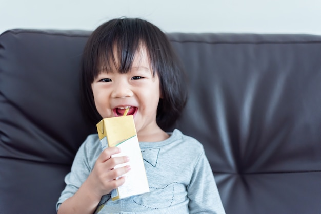 Premium Photo | Happy sweet asian baby child drinking a carton of milk from  box