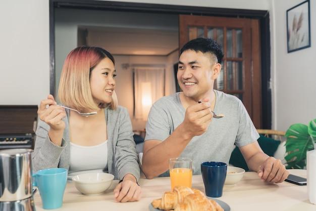 Happy sweet asian couple having breakfast, cereal in milk, bread and drinking orange juice Free Photo