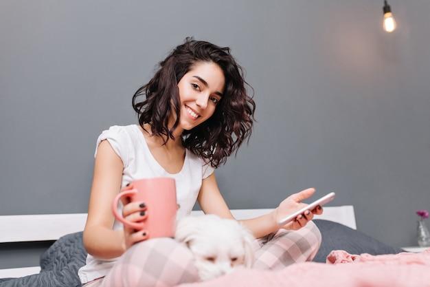 モダンなアパートメントの犬と一緒にベッドでゾッとパジャマでブルネットの巻き毛をカットで若い美しい女性の幸せな甘い瞬間。笑顔、ネットサーフィン、家でのんびり 無料写真