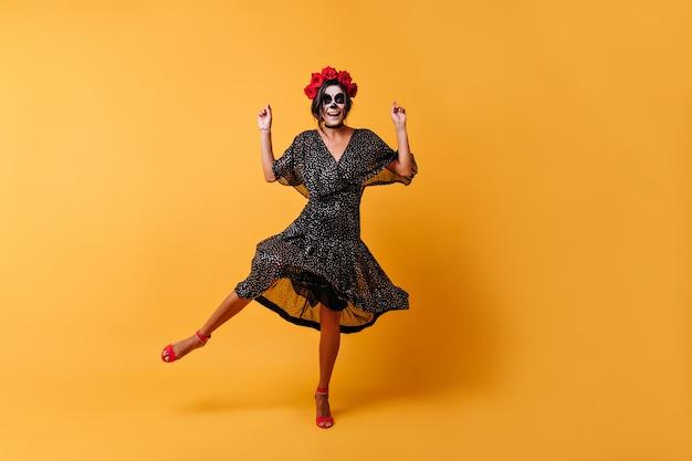 La donna abbronzata felice si diverte a ballare nell'immagine di halloween. inquadratura a figura intera di una ragazza in abito nero e con rose tra i capelli Foto Gratuite